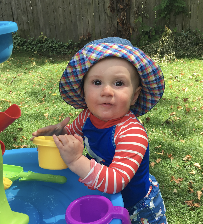 a baby poses for a photo wearing a plaid-lined bucket hat.