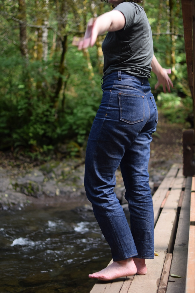 woman poses in high-waisted, rigid denim Dawn jeans, a pattern from Megan Nielsen