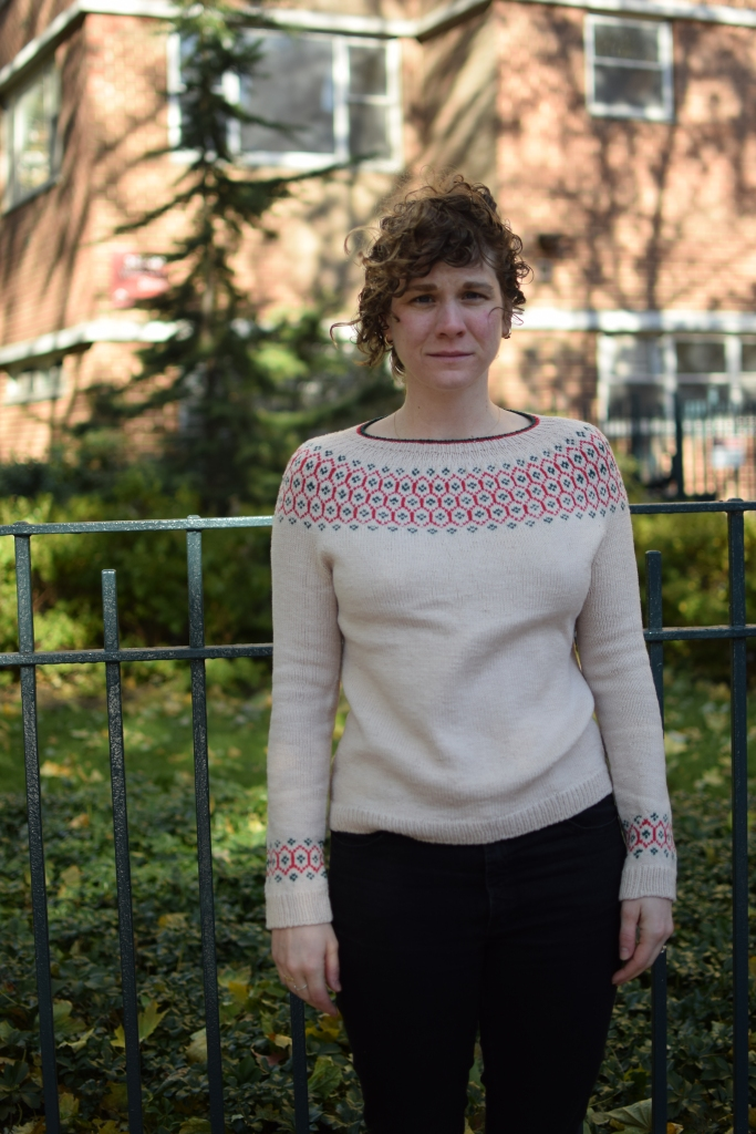 a woman stands in the city, wearing a hand-knitted sweater.