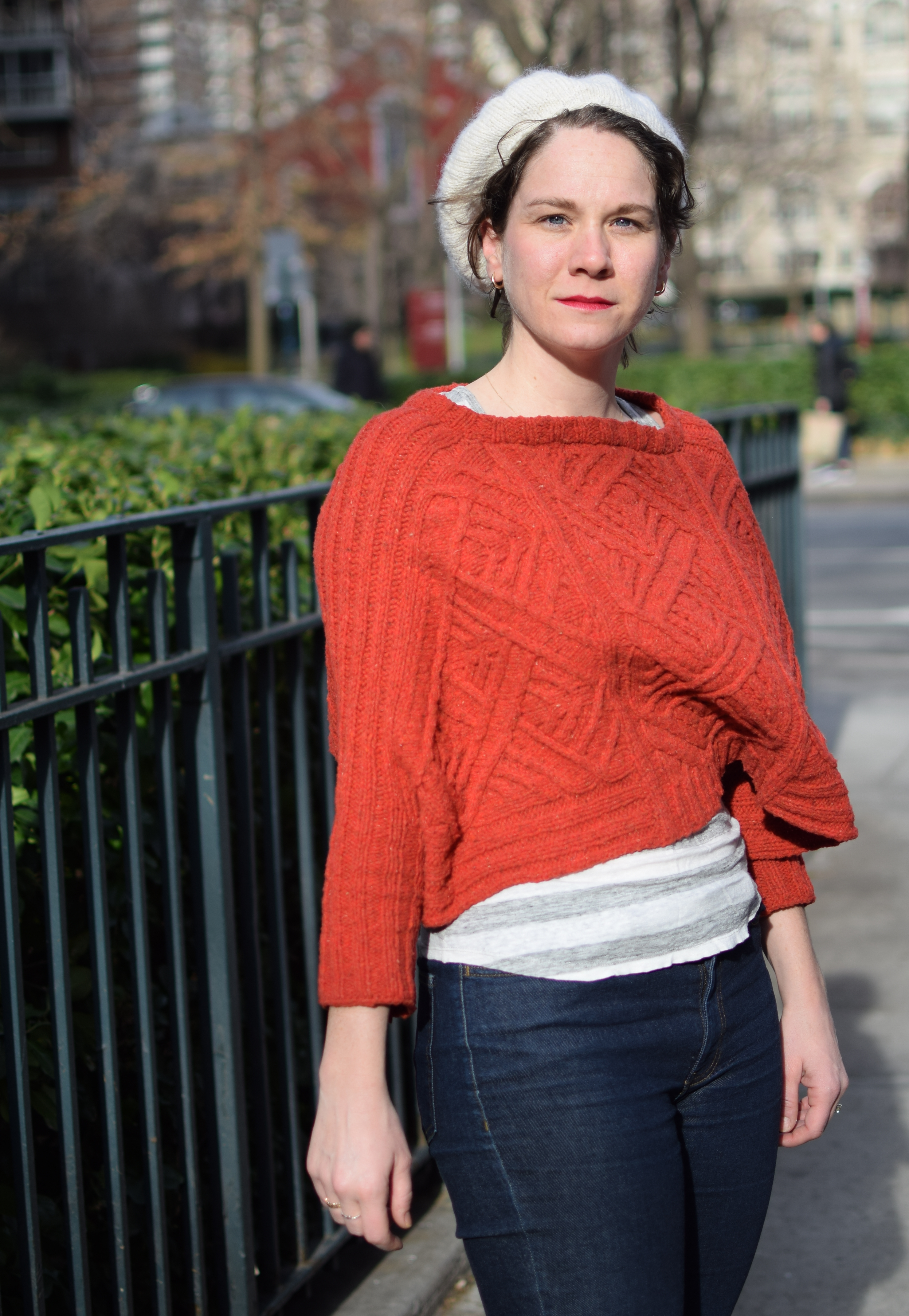 a woman poses on a windy day in a red sweater.