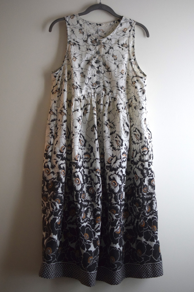 a handmade black and white floral dress on a hanger.