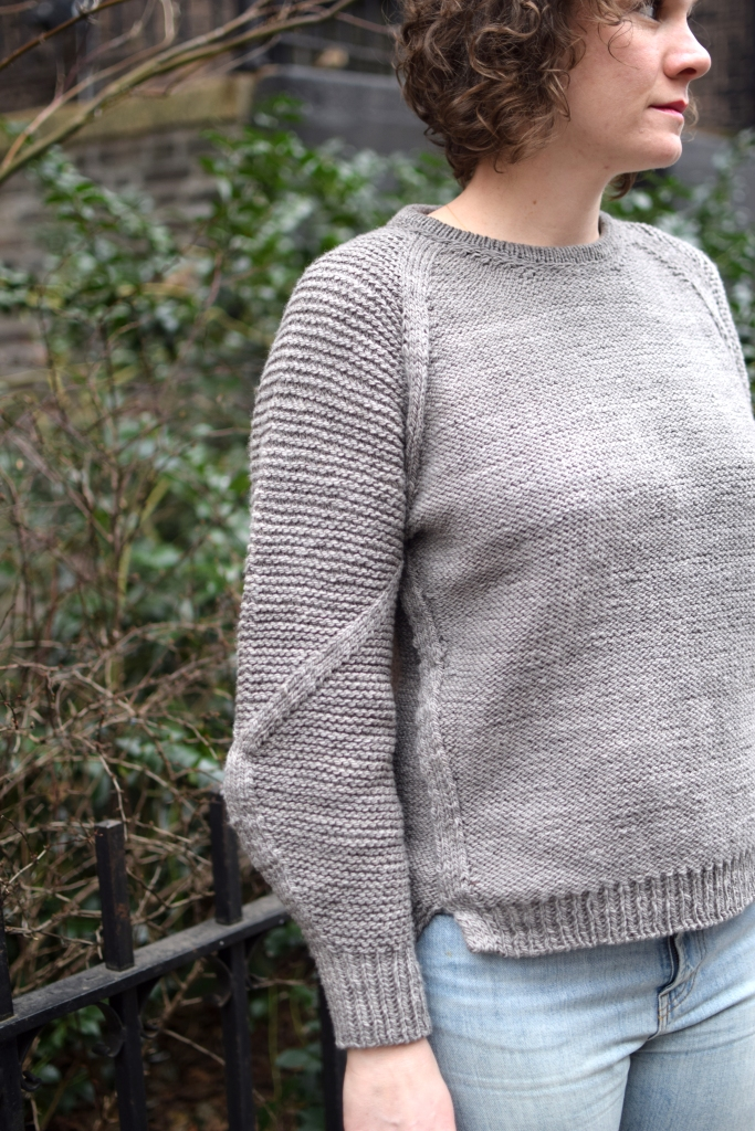 a woman stares off camera, wearing a hand knit gray sweater.