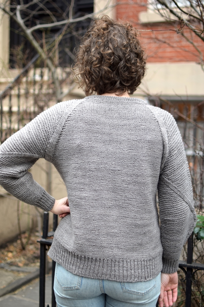 back view of a woman wearing a sweater she knit.