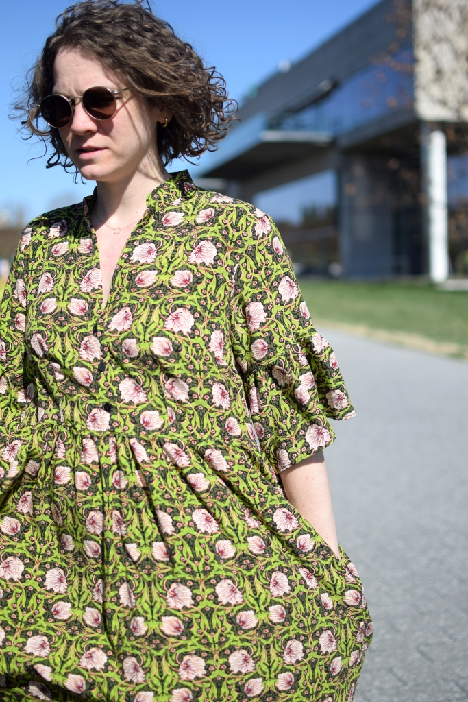 a girl wearing a green and pink floral dress in the bright sun.