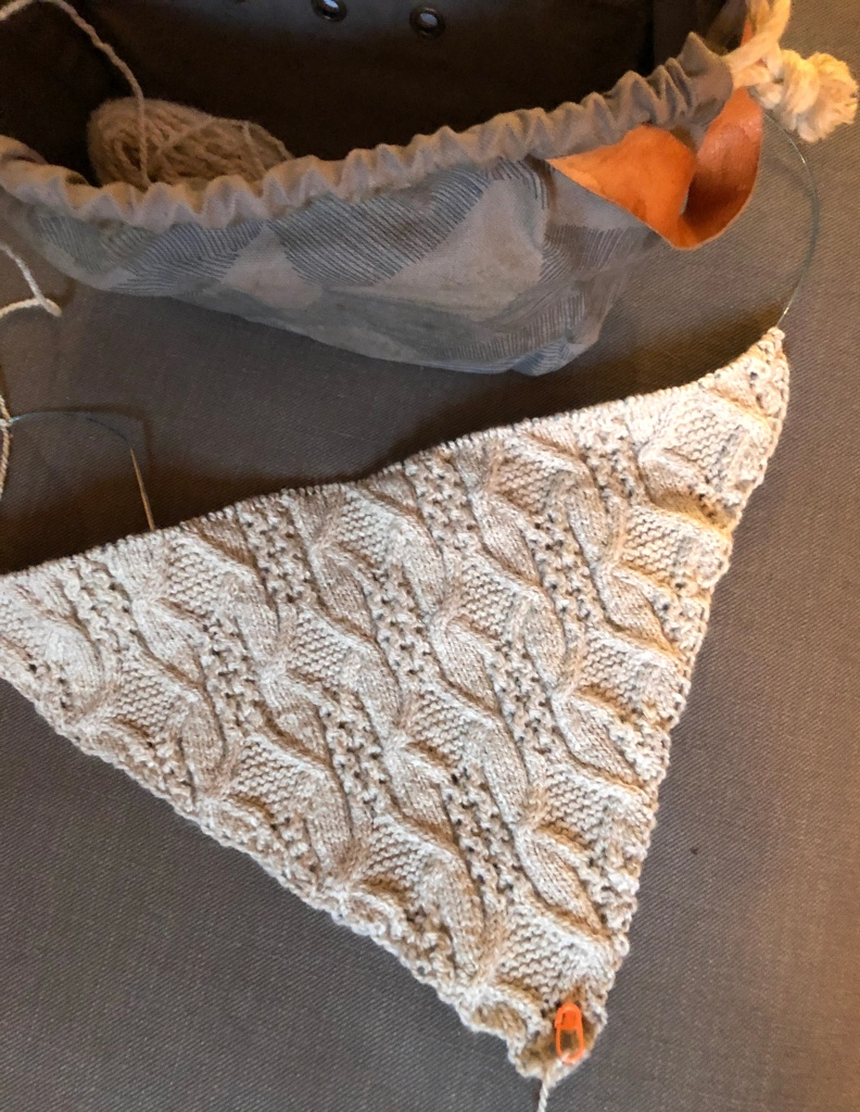 an in-progress photo of a hand knitted light gray shawl