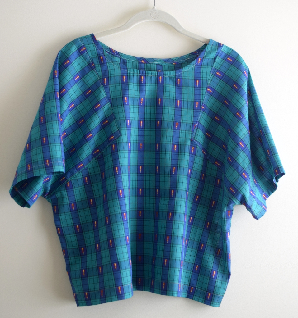a blue and green plaid top on a hanger.