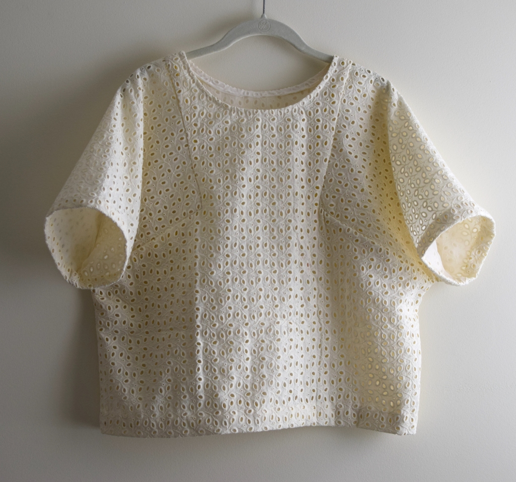 a white eyelet top on a hanger.