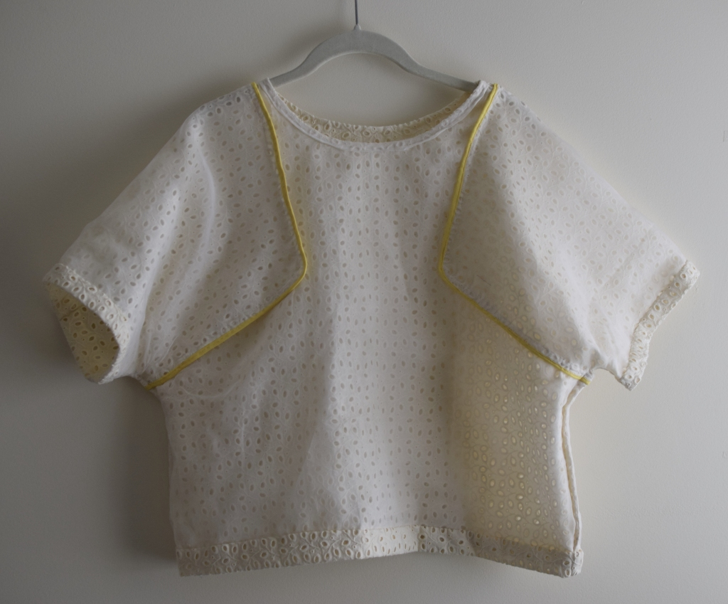 an inside-out eyelet top on a hanger.