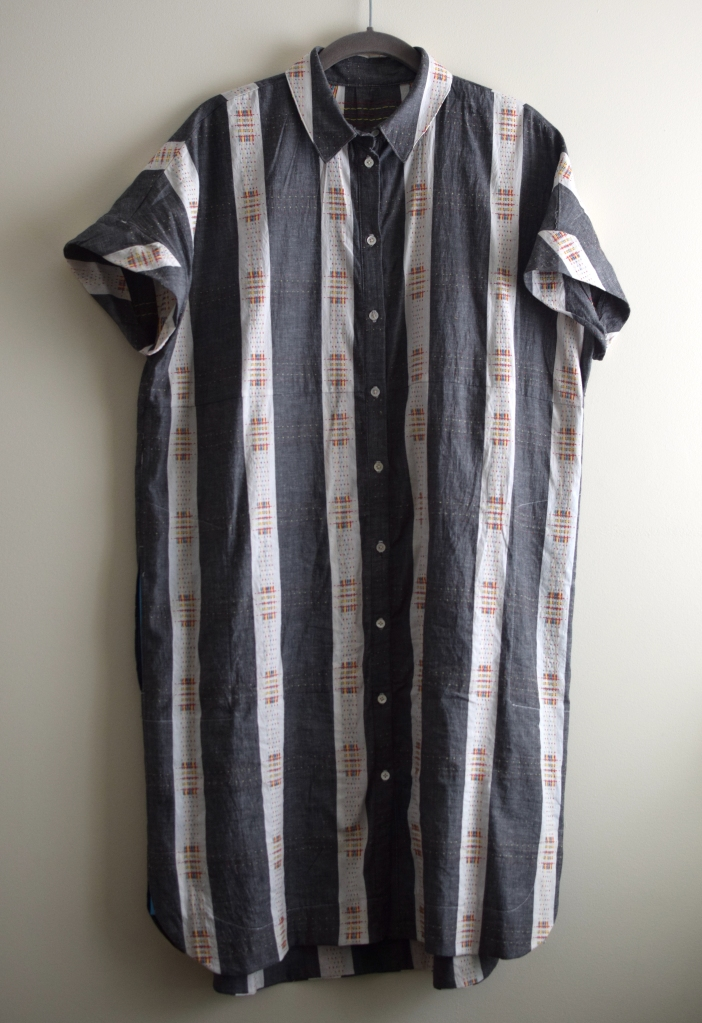 a button-down shirtdress on a hanger.