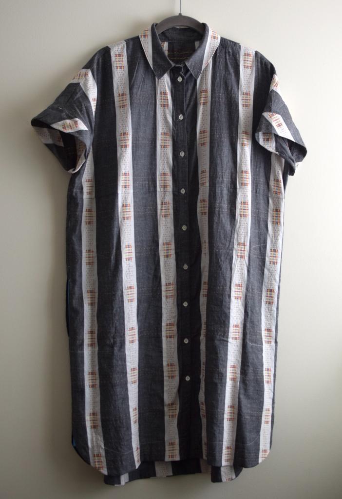 a button-down shirtdress on a hanger.