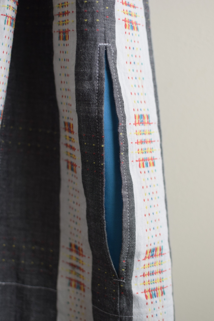 a closeup of the shirtdress pocket with a contrasting lining.