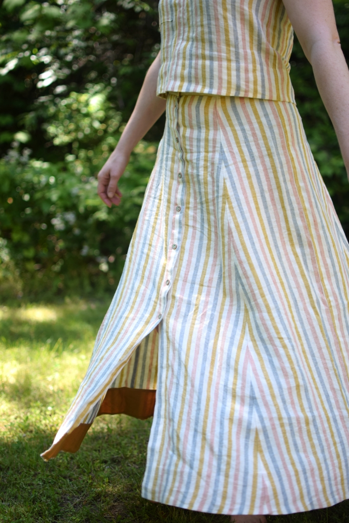 a woman twirls in a striped Wiksten tank top and Fumeterre skirt from Deer and Doe.