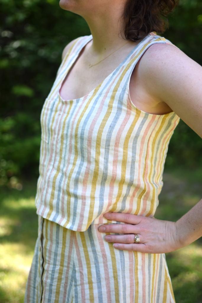a woman stands outside, wearing a striped Wiksten tank.