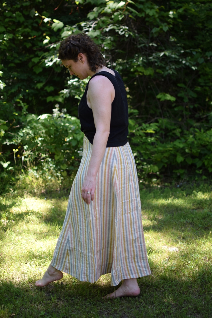 a woman stands outside wearing a long striped Fumeterre skirt from Deer and Doe.