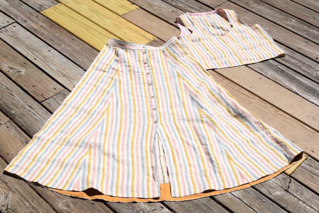A Wiksten tank top and Fumeterre skirt from Deer and Doe laid on a deck.