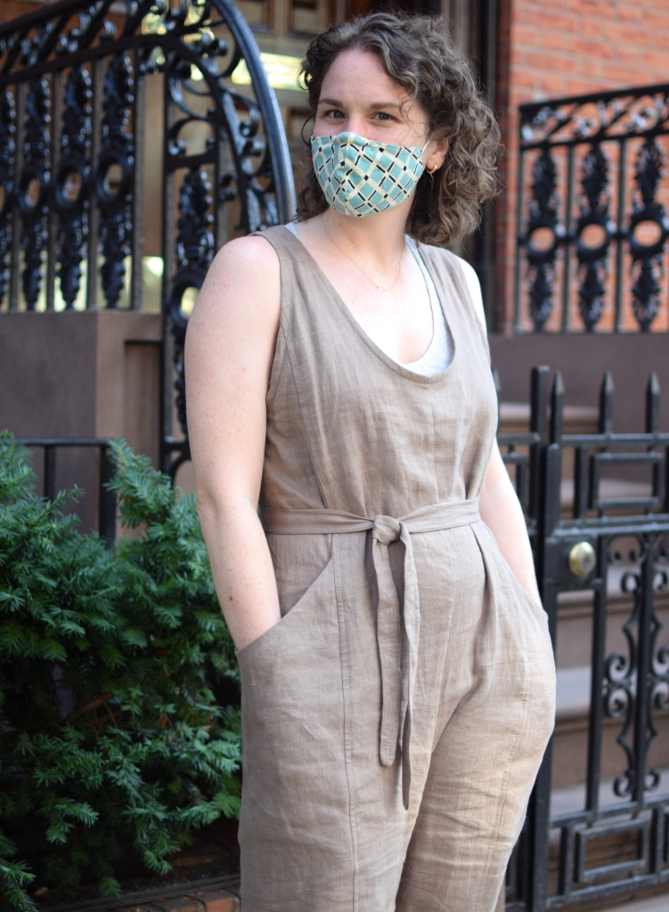 A woman stands on a city sidewalk, wearing a taupe jumpsuit. #esmadebyme
