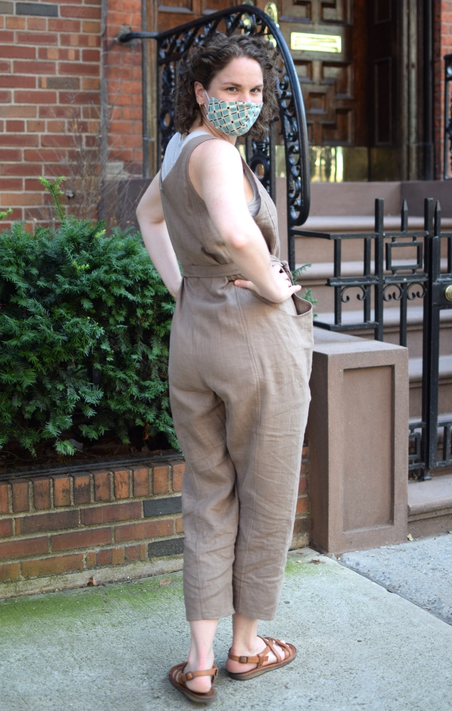 a woman stands on a sidewalk wearing a handmade Elizabeth Suzann clyde jumpsuit